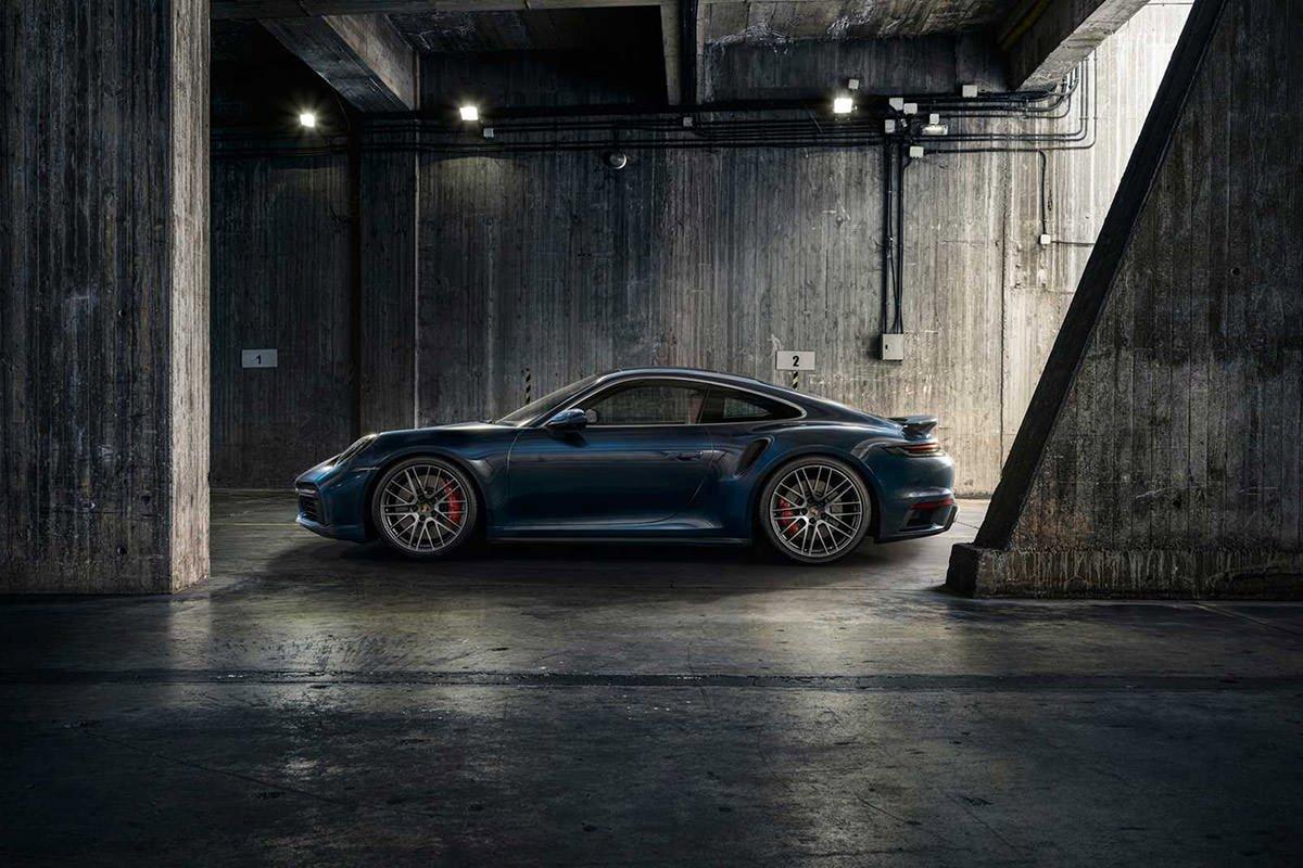نمای جانبی خودرو پورشه 911 توربو 2021 / 2021 Porsche 911 Turbo در پارکینگ با رنگ آبی تیره